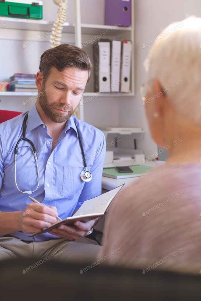 Front view of a Caucasian male doctor interacting with a senior woman in a clinic