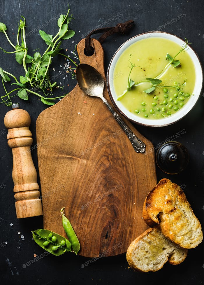Fresh homemade pea cream soup with bread, copy space