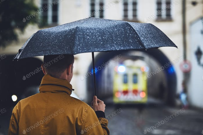 Man with umbrella looking at leaving ambulance car