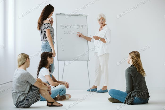 Senior psychotherapist writes the rules of group consultations for women on a white board