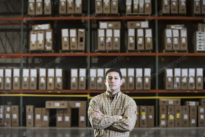 Warehouse worker by a rack of stock in a distribution warehouse.