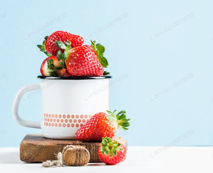 Fresh ripe red strawberries in country style enamel mug