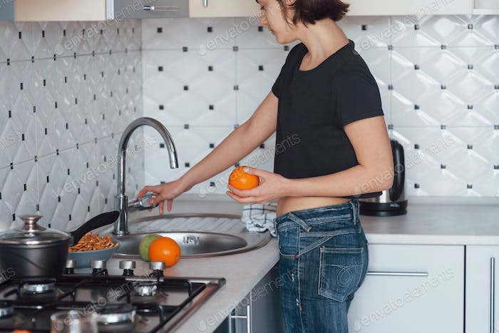 Orange in hand. Girl in the modern kitchen at home at her weekend time in the morning