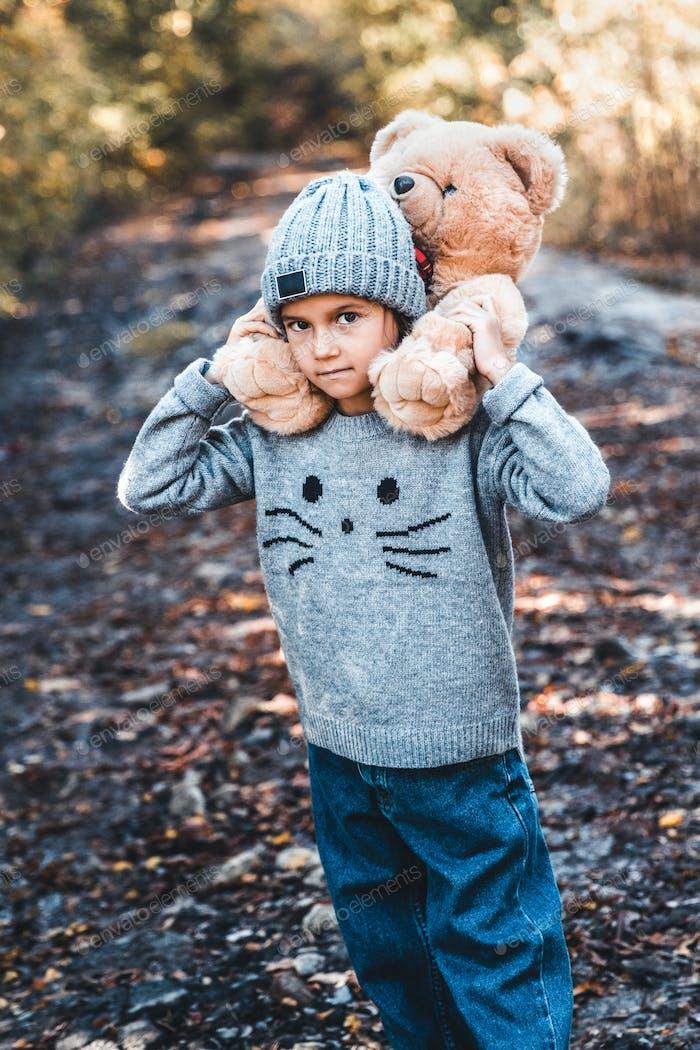 A teddy bear sits on the back of a little girl. Autumn, friendship