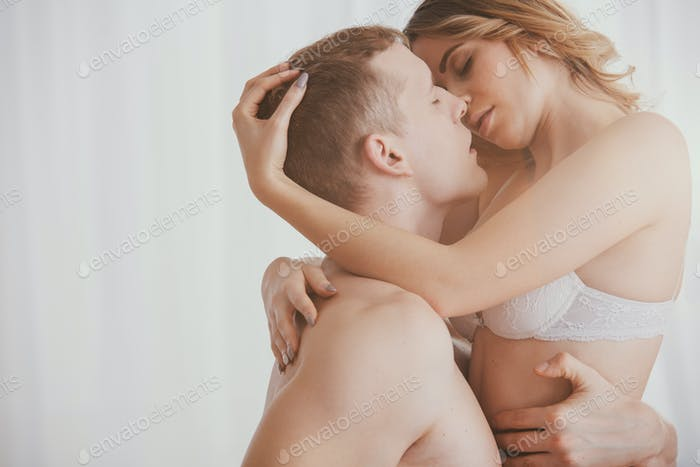 Romantic couple kissing each other and embracing during sensual