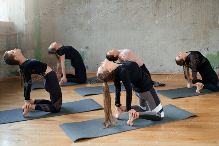 Young women practicing yoga in hall