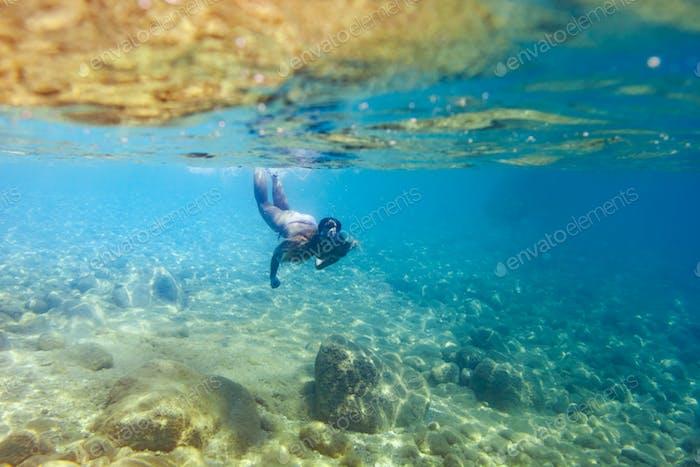Junge Frau schnorchelt und taucht im tropischen Meer