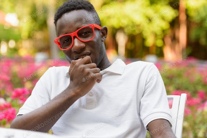 Young African man with eyeglasses thinking and sitting at the park outdoors