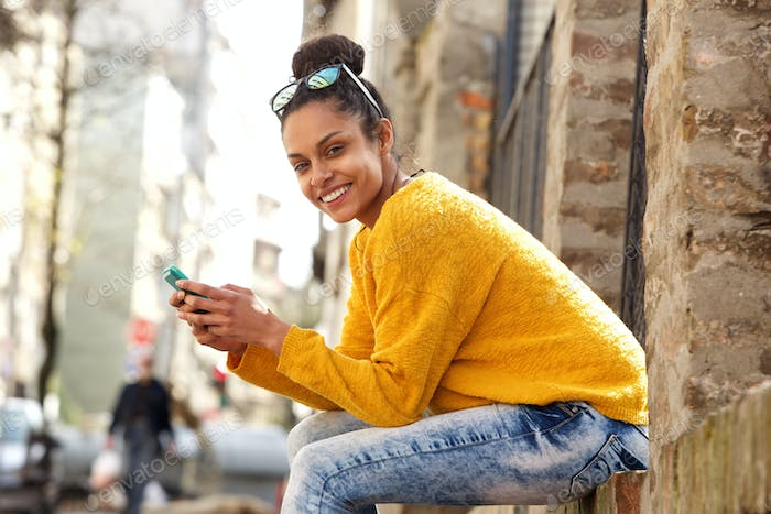 Beautiful young woman sitting by a street with mobile phone
