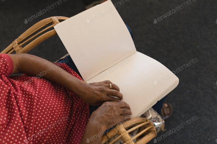 Mid section of blind senior man reading a braille book while sitting on chairat nursing home
