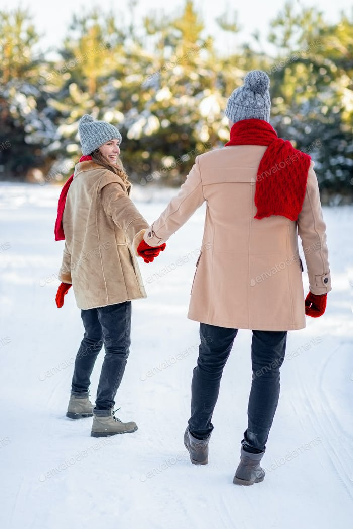 Rear view of romantic lovers enjoying snowy winter day