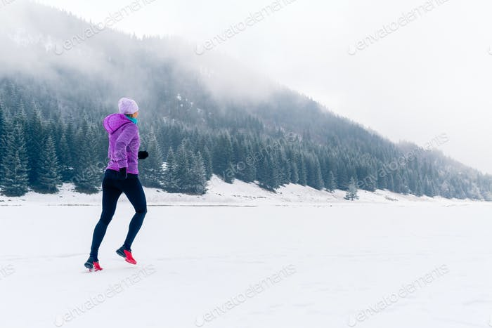 Woman running on winter trail, fitness inspiration and motivatio