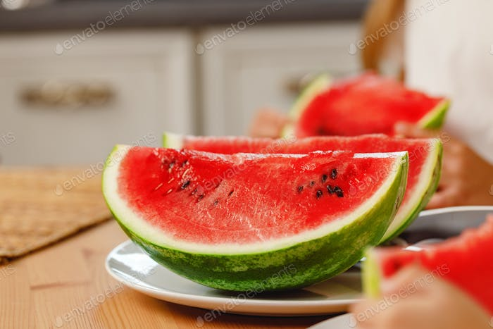 Semi-circle slices of ripe watermelon on wooden board