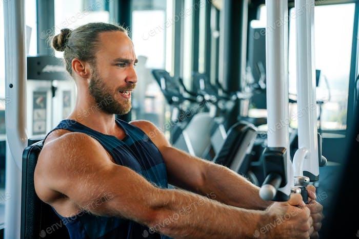 Fit Mann trainieren in der Turnhalle auf einer Maschine