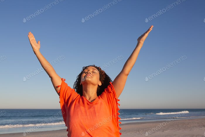 Front view of beautiful mixed race woman with arms up standing on beach in the sunshine