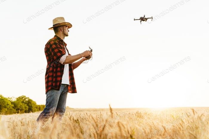 Image of focused handsome man using drone while standing at cereal field