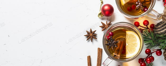 Winter hot tea with fruit, berries and spices on white table