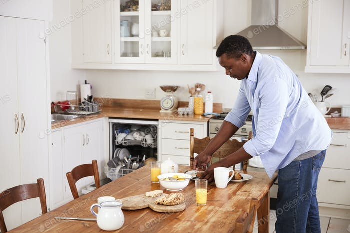 Man Clearing Breakfast Table And Loading Dishwasher