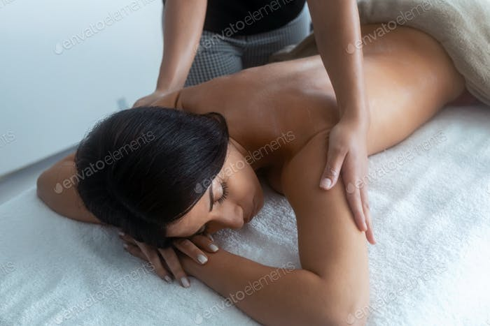 Young woman removing the chocolate cream to a pretty woman on the spa center.