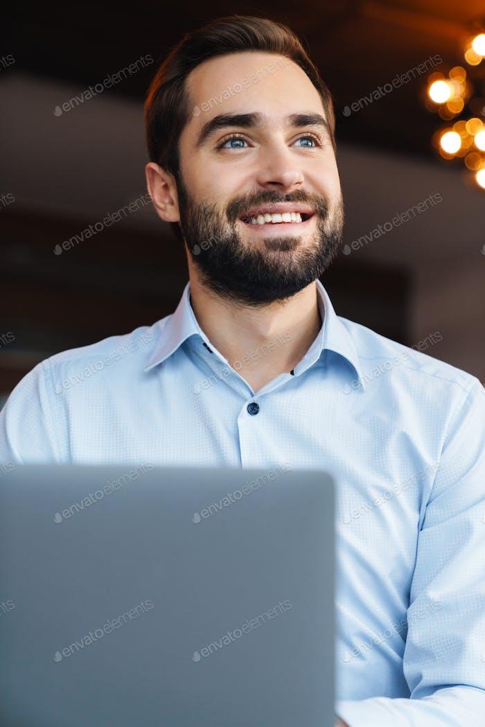 Porträt von jungen Geschäftsmann mit Laptop während der Arbeit im Büro