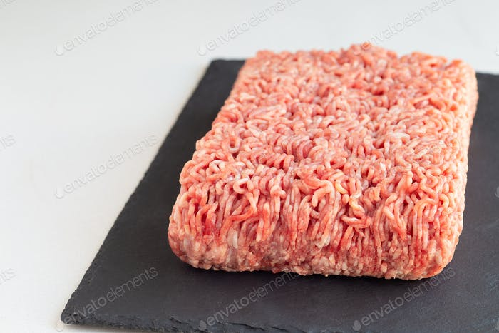 Minced meat from pork and beef, ground meat on dark slate board,