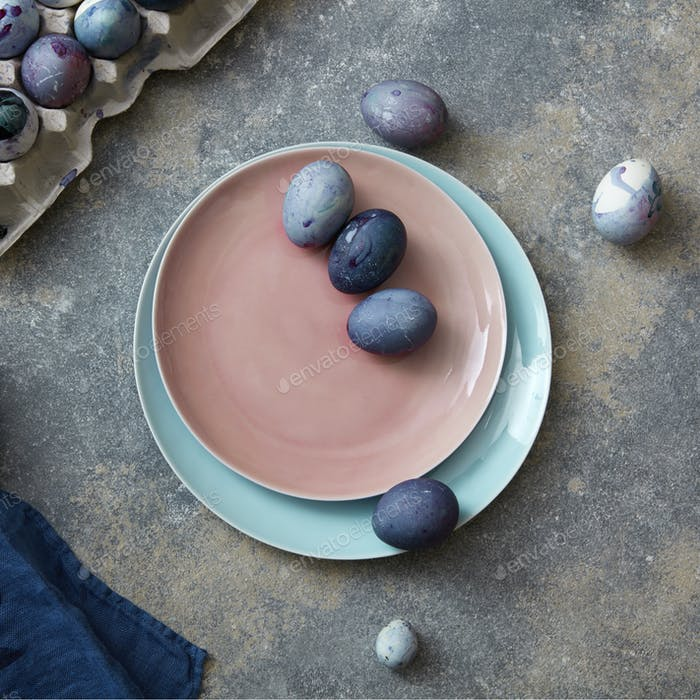 Glazed ceramic plate in a color of Living Coral Pantone with painted violet Easter eggs on a gray