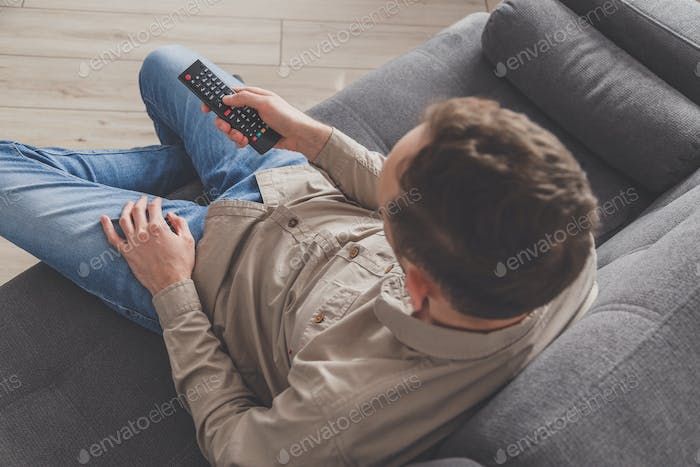 Man lying on sofa watching TV at home. Social distancing