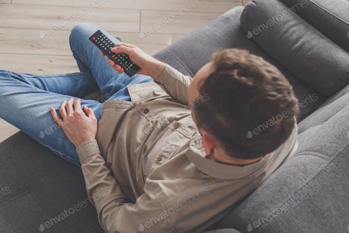 Mann liegend auf dem Sofa Fernsehen zu Hause. Soziale Distanzierung