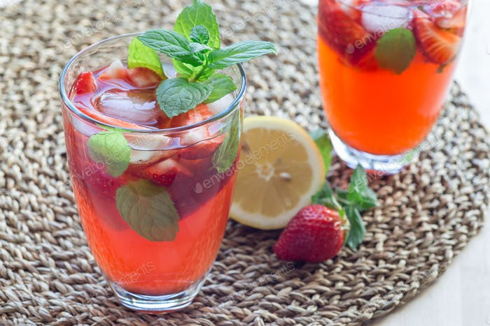 Homemade iced tea with strawberries and mint on wooden table, ho