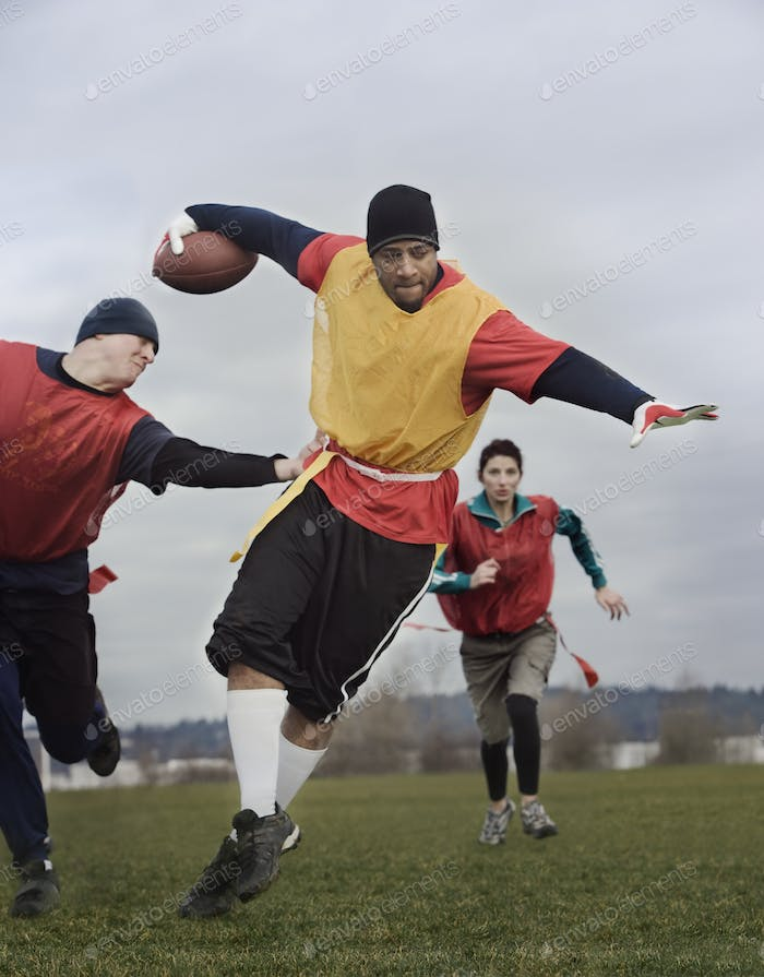 Black man running with the football and being chased by opponents in a non-contact flag football