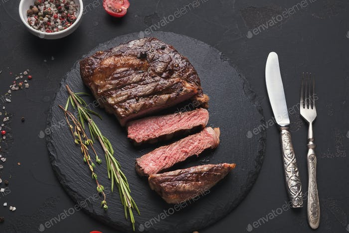Rib eye steak and spices on black background