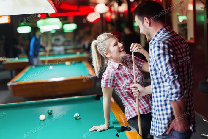 Young couple enjoying playing snooker on date