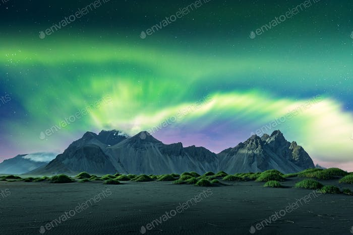 Aurora borealis Northern lights over black sand desert dunes