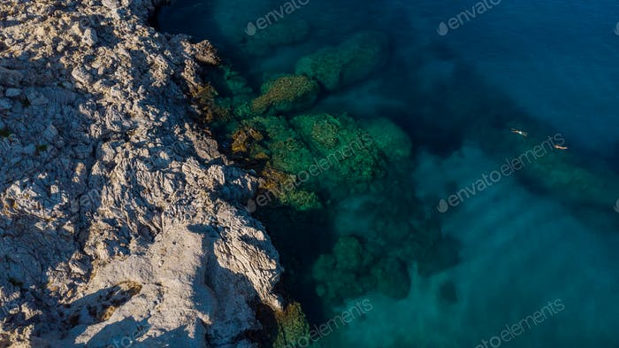 Blue Water and Rocky Beach, Top Down View, People Swim in Sea