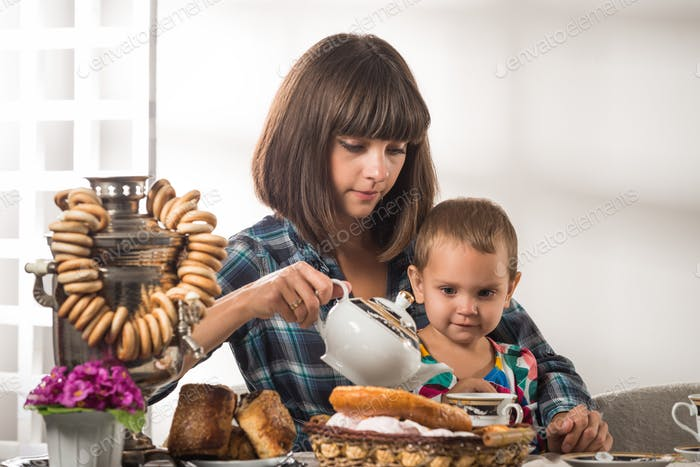Cute caring mother pours tea to little cute son