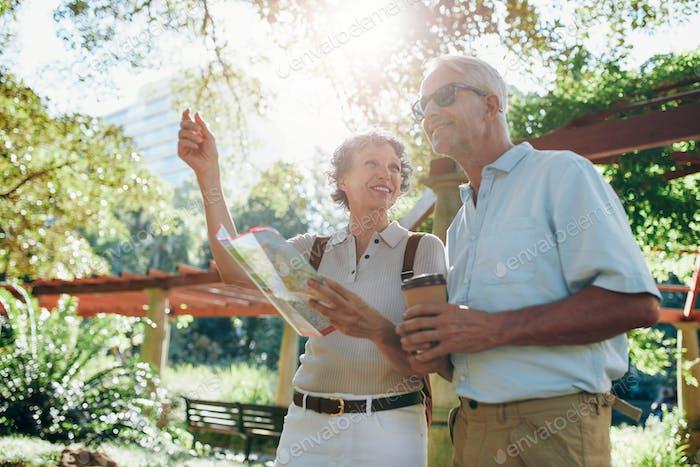 Happy senior tourists reading a map