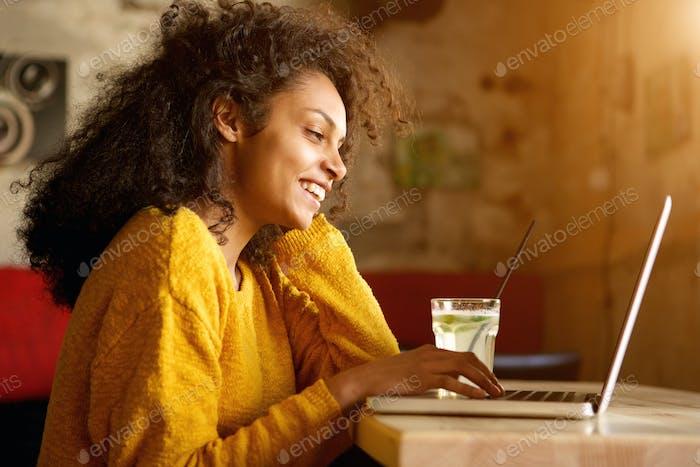Fröhliche junge Frau arbeitet am Laptop im Café