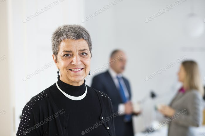 Portrait of mature businesswoman smiling while colleagues discussing in office