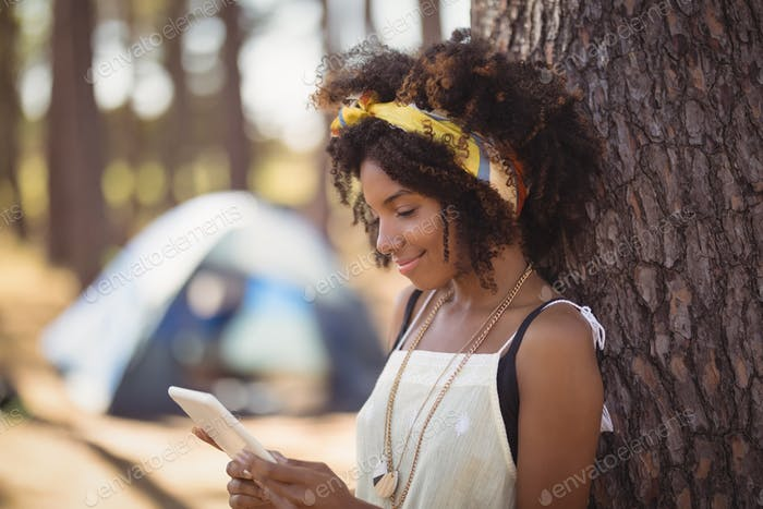 Young woman using smart phone while standing by tree trunk