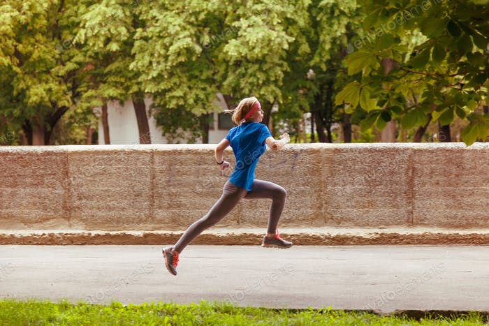 Young sporty woman running in the summer city park