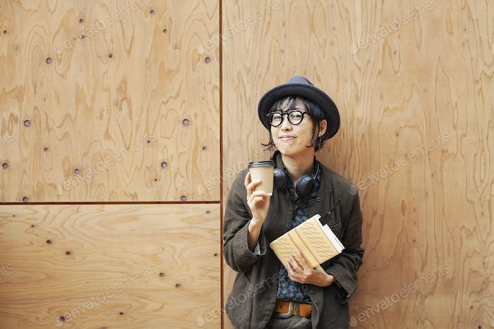 Japanese woman wearing glasses and hat standing outside Eco Cafe, holding paper cup and notebook.