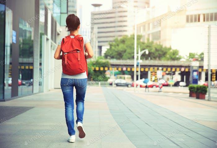 Woman with rucksack walking on street