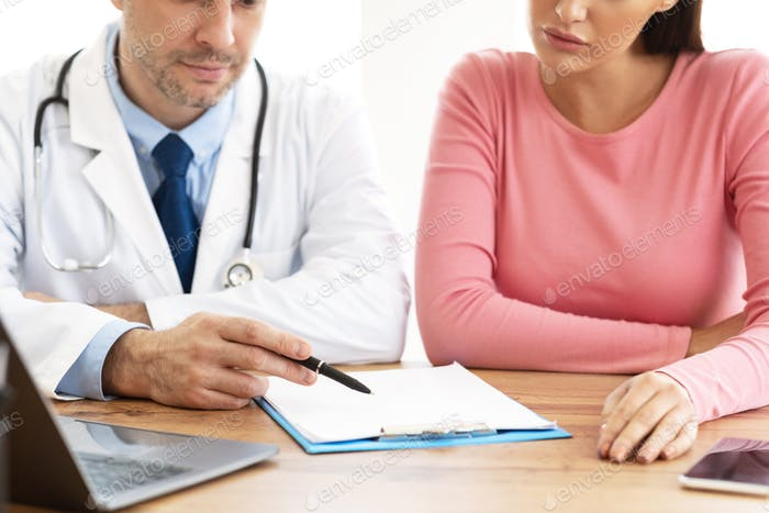 Male experienced doctor consulting his female patient