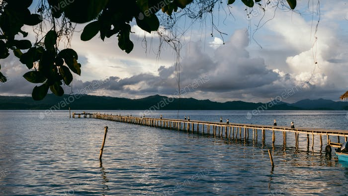 Cloudscape with wooden pier in kri island before tropical thunderstorm. Raja Ampat archipelago, West