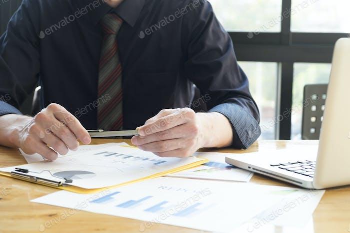 Bolígrafo de hombre de negocios que analiza gráficos de inversión con laptop.