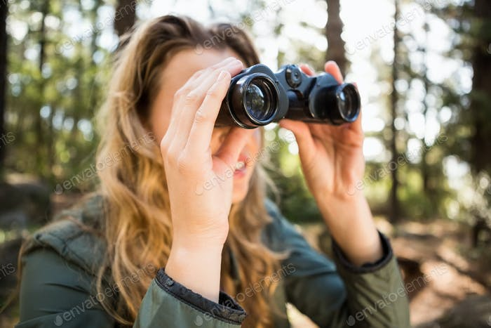 Blonde hiker looking through binoculars in the nature