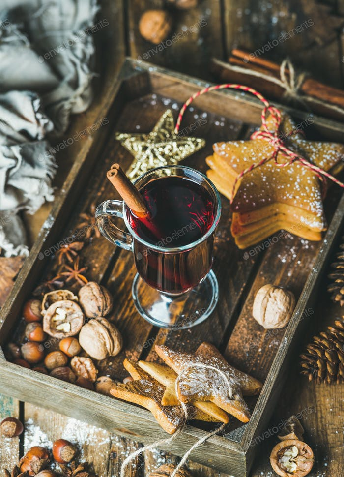 Glass of mulled wine, gingerbread cookies, spices in wooden tray