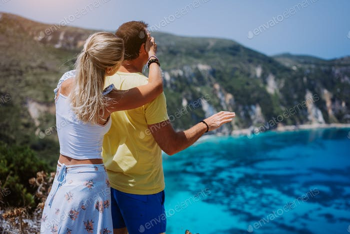Petani view point young woman closing her boyfriend eyes in front of gorgeous seascape panorama