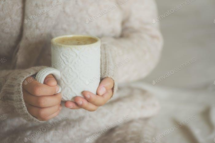 Famale Hände halten eine gemütliche Keramik handgemachte Tasse mit Kaffee. Winter- und Weihnachtszeitkonzept