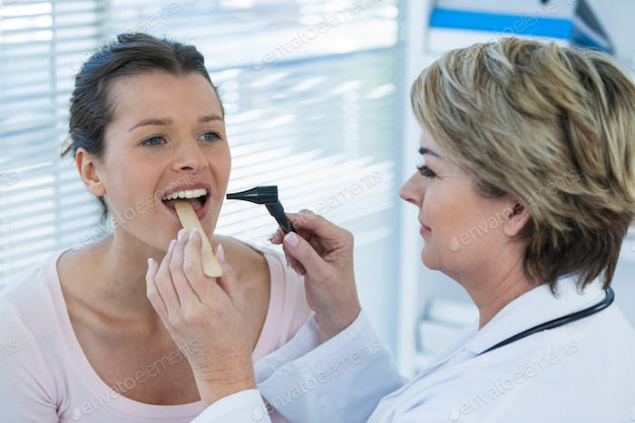 Doctor examining patients teeth with otoscope